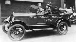 In 1927, Edsel Ford is in the driver's seat with his 64-year-old father, Henry Ford, next to hom and Charles Sorensen in the back seat as the drive the 15-millionth Model T out of the Highland Park Plant