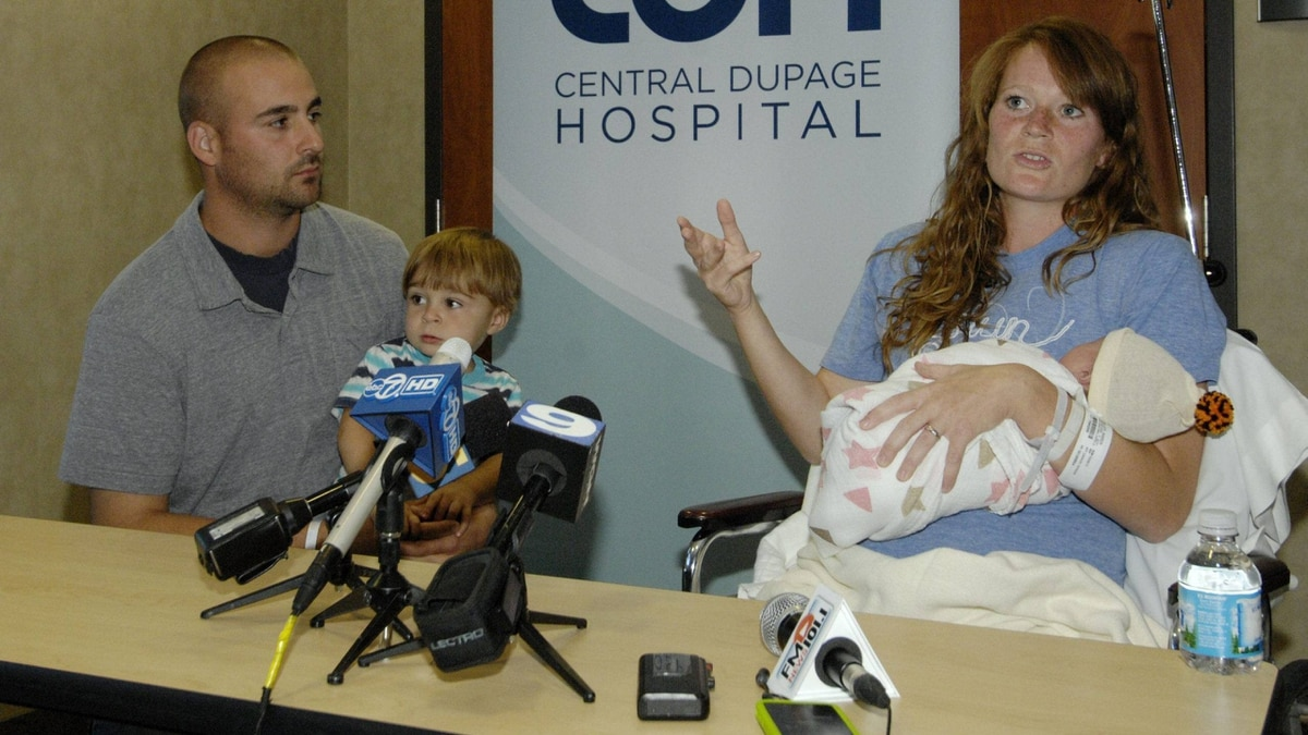 Amber Miller, of Westchester, Ill., gestures during a news conference as she holds her baby at Central DuPage Hospital in Winfield, Ill., Monday Oct. 10, 2011.