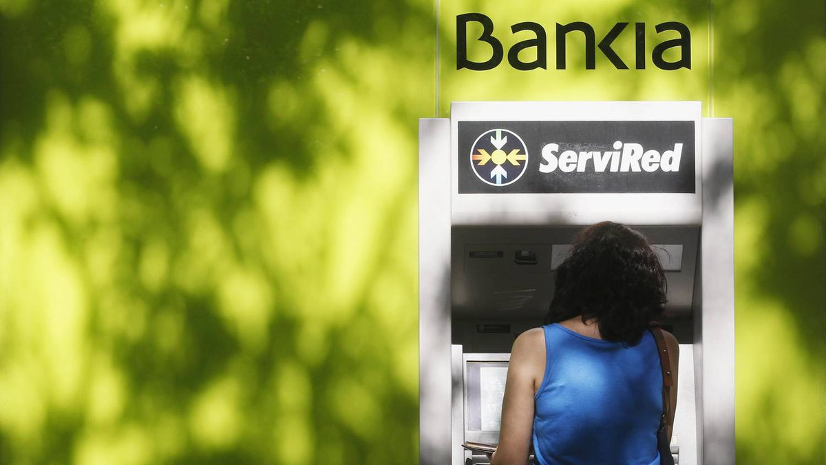 A woman withdraws money from an ATM machine at Spain's lender bank Bankia in Madrid