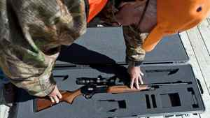 A rifle owner puts guns back in its case at a hunting camp near Ottawa on Sept. 15, 2010.