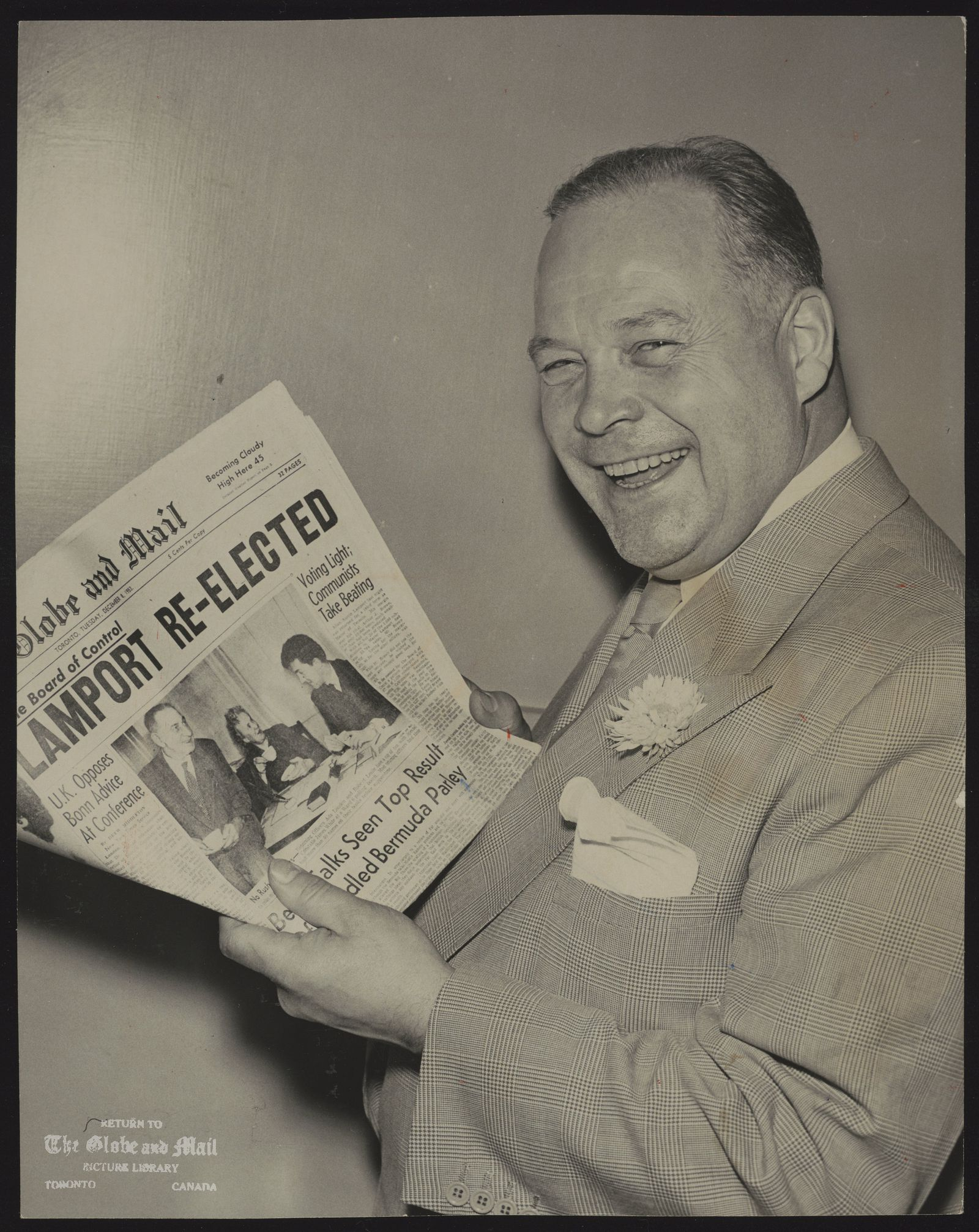 ALLAN LAMPORT Beaming happily despite a drastic cut in his margin of victory, Mayor Lamport reads The Globe And Mail headline telling of his election to third term. All but one member of Mayor Lamport's 1953 council were returned with him. Ald. Chambers had retired.