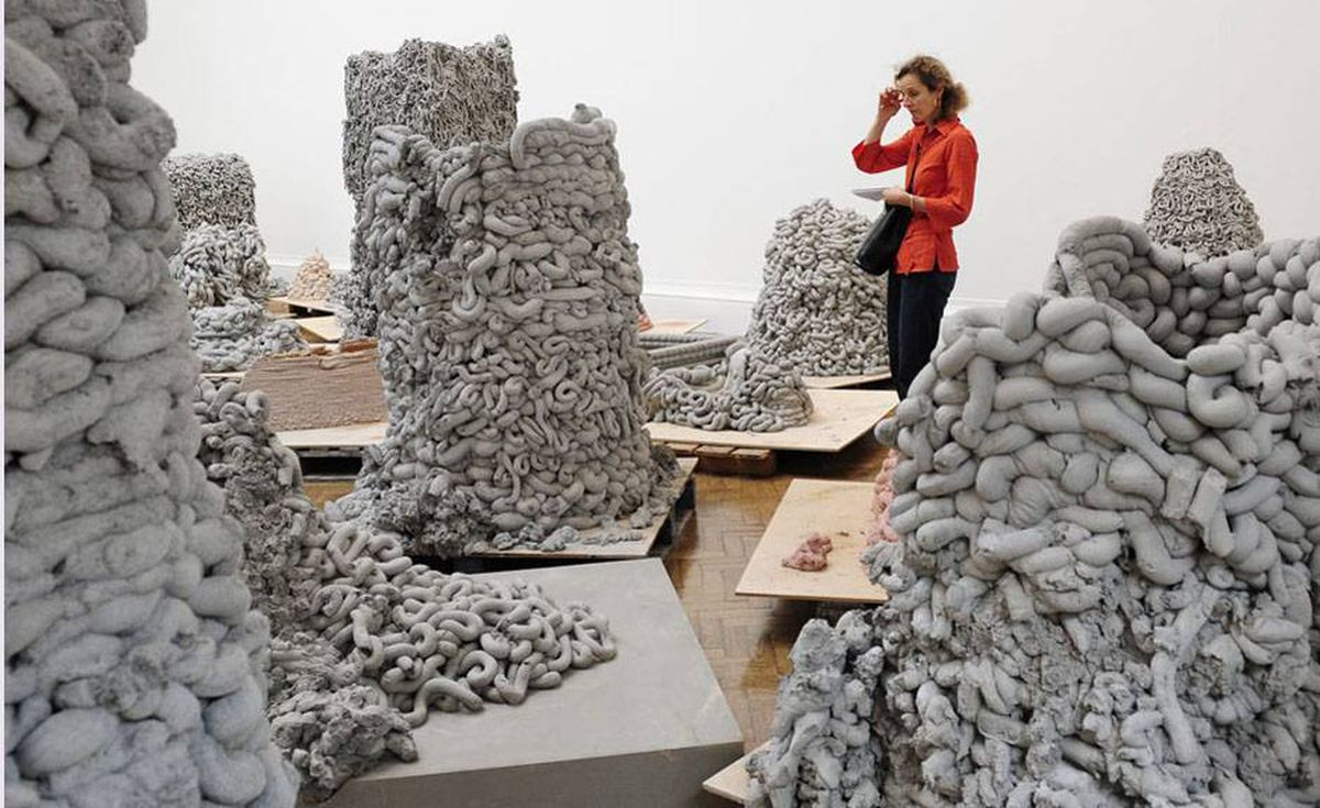 A visitor views sculptures by British artist Anish Kapoor.