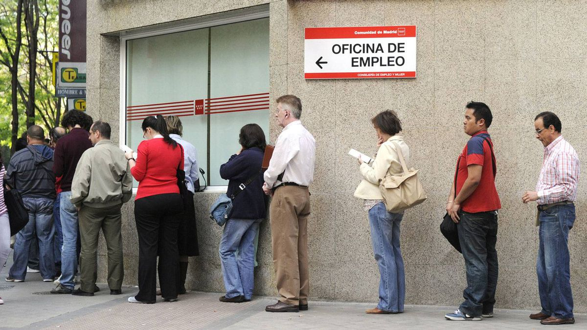 People wait in line at a government employment office in the centre of Madrid.