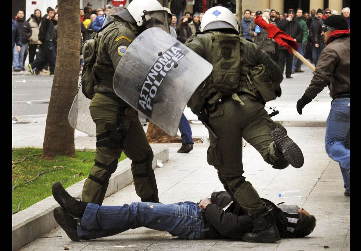 A riot policeman kicks an anti-austerity protester who fell during clashes in Athens.