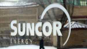 A pedestrian is reflected in a Suncor Energy sign in Calgary, Monday, Feb. 1, 2010.