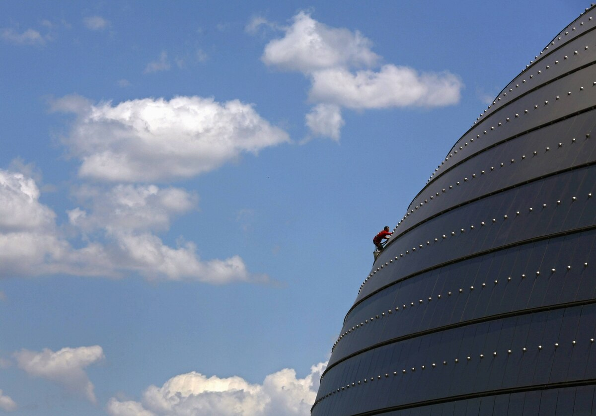 """A worker cleans the roof of the National Grand Theatre, nicknamed """"The Egg"""", on a sunny day in Beijing, China."""