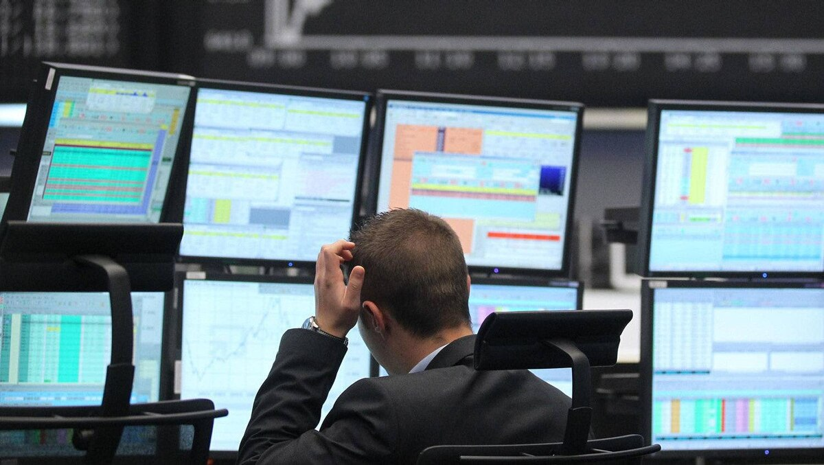 A trader reacts at his desk in front of the DAX board at the Frankfurt stock exchange on Monday. Euro zone blue chips turned positive by mid-session, bouncing back from oversold territory after a knee-jerk reaction to French and German elections.
