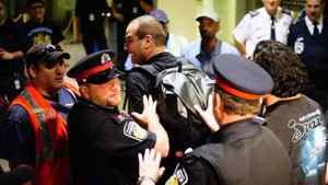 Police remove a person from the area as Air Canada baggage handlers stage a wildcat walkout at Toronto's Pearson International Airport early Friday March 23.