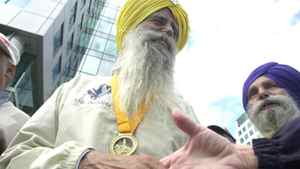 Fauja Singh, 93, being congratulatred after setting a record in his age class in the Toronto Waterfront marathon in this Sept. 28, 2003 file photo..