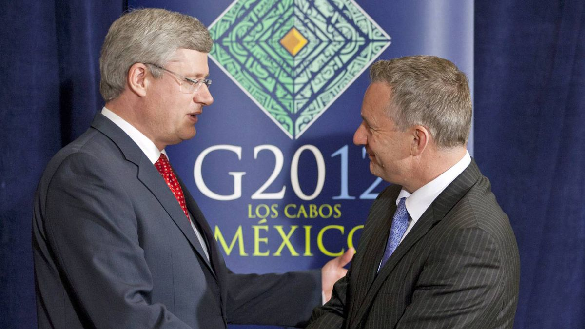 Prime Minister Stephen Harper shakes hands with International Trade Minister Ed Fast after a news conference at the G20 Summit in Los Cabos, Mexico, on June 19, 2012.