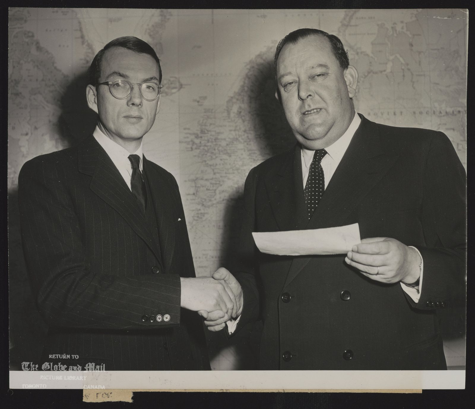 CANADIAN CHECK FOR U.N. RELIEF. JOHN W. HOLMES, UNITED NATIONS DELEGATE FOR CANADA, PRESENTS A CHECK FOR EIGHT MILLION DOLLARS TO U.N. SECRETARY GENERAL TRYGVE L E (RIGHT), FOR THE U.N. RELIEF FUND. SEVEN AND A QUARTER MILLIONS ARE FOR KOREAN RELIEF AND REHABILITATION AND THREE QUARTERS OF A MILLION DOLLARS FOR ISRAEL RELIEF. THE PRESENTATION, APRIL 5, IS BEING MADE IN L E'S OFFICE AT U.N. HEADQUARTERS, NEW YORK CITY. 4/5/51 [1951]