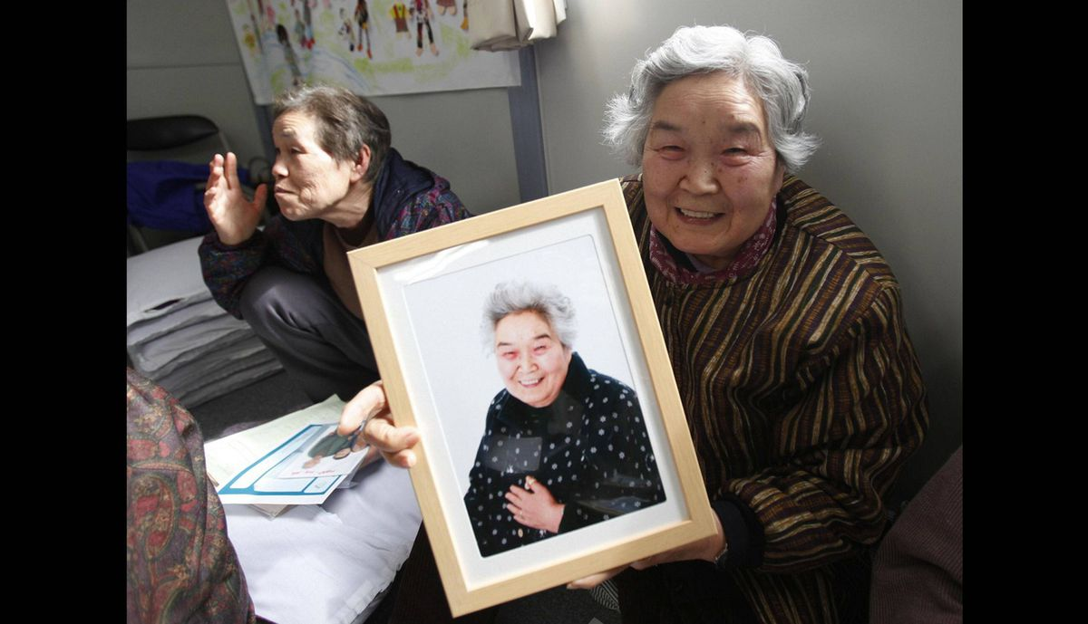 Misako Yokota shows her framed portrait after receiving it from 3.11 Portrait Project volunteers at the Midorigaoka temporary shelter in Koriyama, Fukushima prefecture in the Tohoku region, February 27, 2012. The project was conceived by photographer Nobuyuki Kobayashi who takes portraits of Japan's earthquake survivors. The portraits are then sent to schoolchildren from non-disaster areas, who frame the portraits and send them back to the survivors along with personal messages of support.