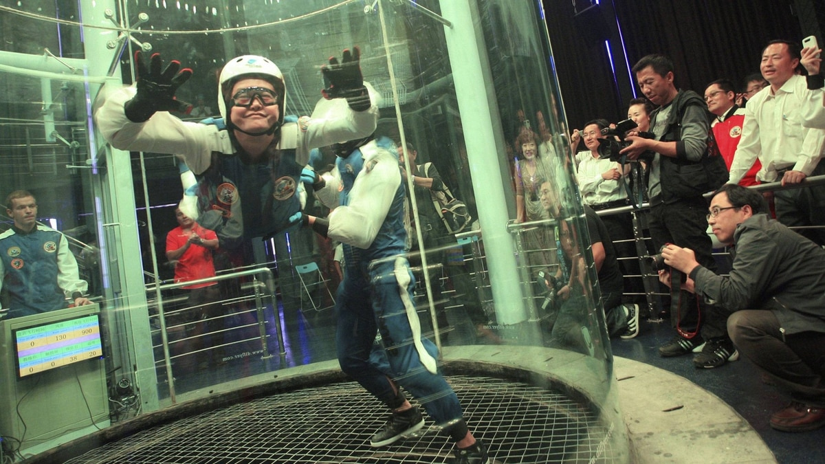 A woman floats with the help of an instructor inside a vertical wind tunnel for visitors to try a body-flying experience at a tourist resort in Dalian, Liaoning province September 27, 2011.