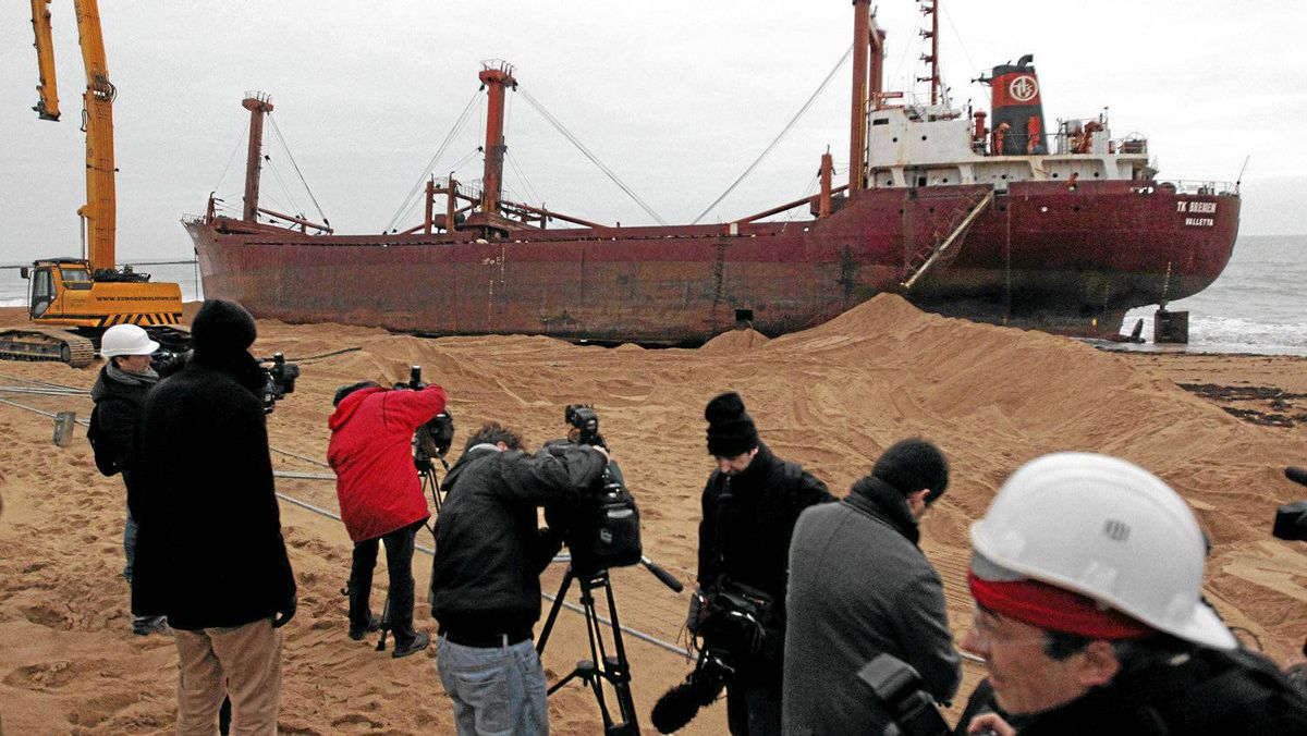 """Members of the media are seen in front of the Maltese-registered cargo ship the TK Bremen. The maritime prefecture spokesman said dismantling the ship would be a complex operation in what is an environmentally-protected zone. The ship would be cut up and the pieces loaded onto trucks. """"The objective is to restore the beach and the dunes by [next year's] Easter holidays,"""" he added."""