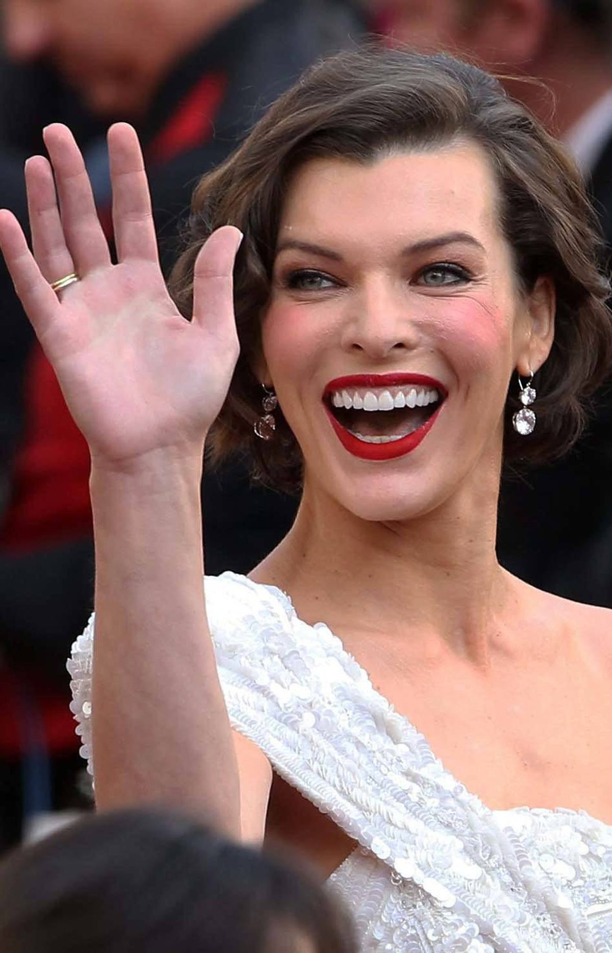 Milla Jovovich cracks her makeup on the Oscars red carpet on Sunday.