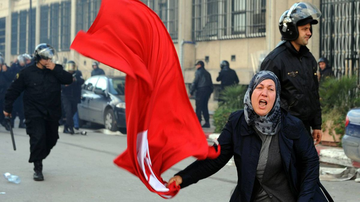 A Tunisian woman waves the national flag in front of the interior ministry during clashes between demonstrators and security forces in Tunis on Jan. 14, 2011.