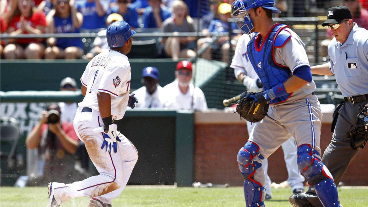 Texas Rangers Elvis Andrus (L) scores on the sacrifice fly by Adrian Beltre (not pictured) as Toronto Blue Jays catcher J.P. Arencibia watches in the second inning of their MLB American League baseball game in Arlington, Texas May 26, 2012. REUTERS/Mike Stone