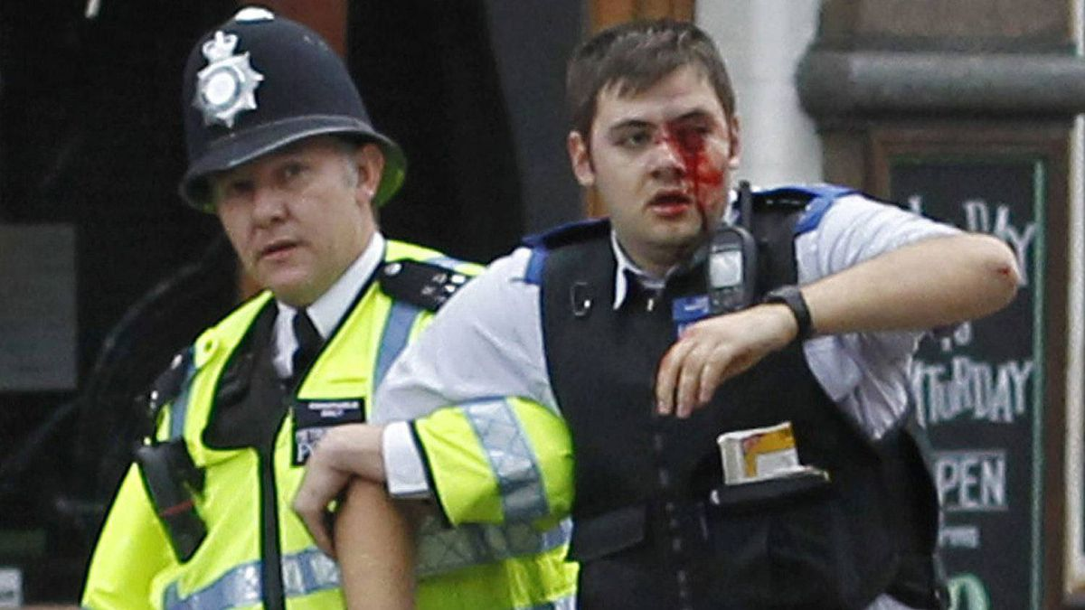 A police officer helps an injured officer as rioters gathered in Croydon, south London, Monday, Aug. 8, 2011. Violence and looting spread across some of London's most impoverished neighborhoods on Monday, with youths setting fire to shops and vehicles, during a third day of rioting in the city that will host next summer's Olympic Games. (AP Photo/Sang Tan)