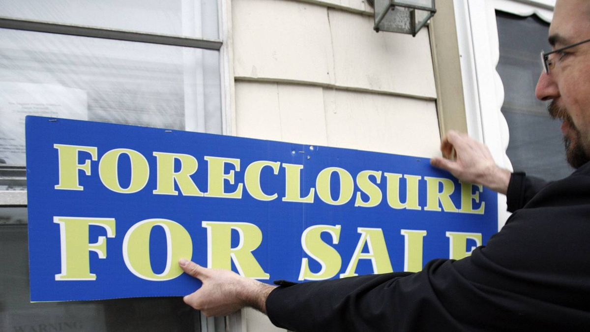A real estate brokerage owner puts a foreclosure sign on a home in a Boston surburb in 2007