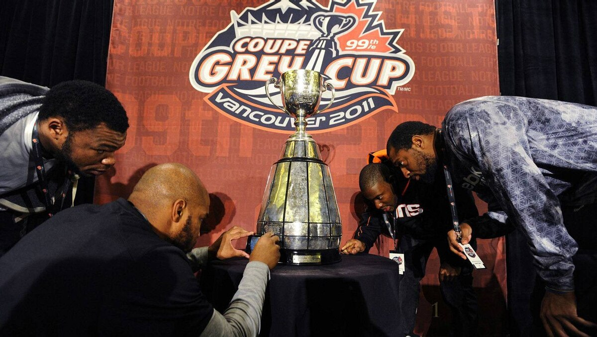 BC Lions' Anthony Reddick (L-R), Anton McKenzie, Shawn Gore and Akeem Foster look at the CFL's Grey Cup during their team lunch in Vancouver, British Columbia, November 24, 2011. The BC Lions will play the Winnipeg Blue Bombers in the CFL's 99th Grey Cup football game on Sunday. REUTERS/Todd Korol