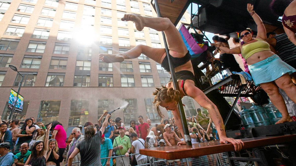 A girl dances on a pole on the Neo Paws float going down Yonge Street.