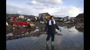 Chieko Chiba walks through the rubble after going to see her destroyed home March 16, 2011 in Kesennuma, Miyagi province, Japan.