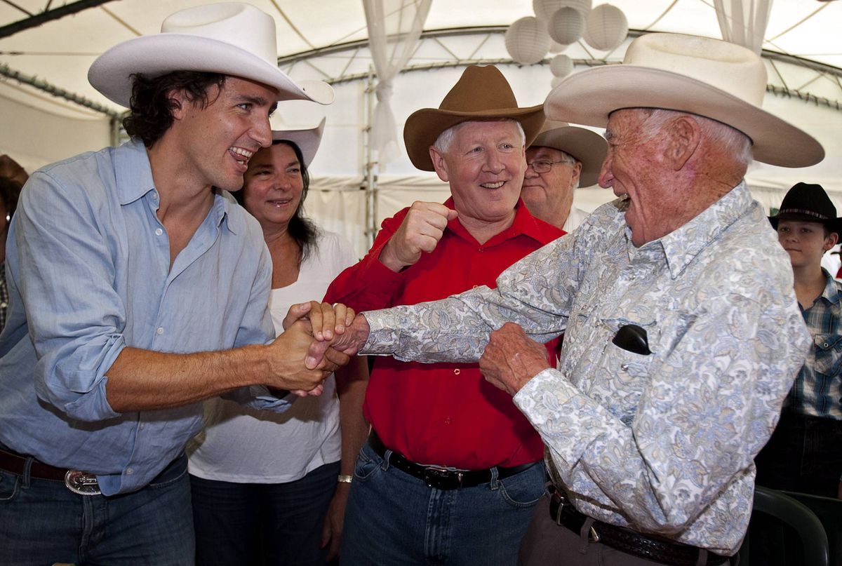 Liberal leader Bob Rae, centre, and MP Justin Trudeau, left, joke with Lyall Curry, 92, while attending the party's annual Stampede breakfast in Calgary, Saturday, July 7, 2012.
