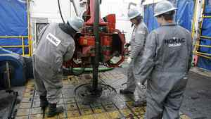 Workers change drilling pipes on the rotary table of a natural gas drilling rig near Towanda, Pa.