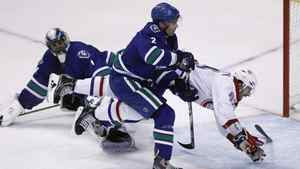 Montreal Canadiens' Max Pacioretty dives through the air after being checked by Vancouver Canucks' Dan Hamhuis in front of Canucks goaltender Roberto Luongo during the third period of their NHL hockey game in Vancouver, British Columbia March 10, 2012.