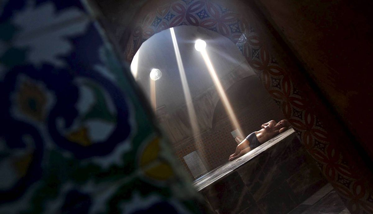 A Libyan man relaxes in the vapor room of the Darguth Turkish bath, or Hammam, in the old city of the Libyan capital of Tripoli on October 6, 2011. TOPSHOTS / AFP PHOTO / KARIM SAHIB (Photo credit should read KARIM SAHIB/AFP/Getty Images)