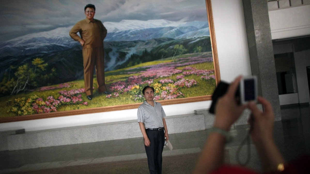 A Chinese visitor poses for a picture next to a portrait of North Korean leader Kim Jong-il at an auditorium in Rason city, northeast of Pyongyang, August 29, 2011.