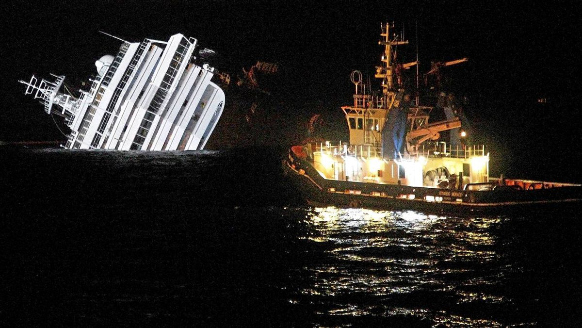 A tugboat approaches the wreck of the Costa Concordia as preparations are made to remove fuel from the stricken cruise ship.