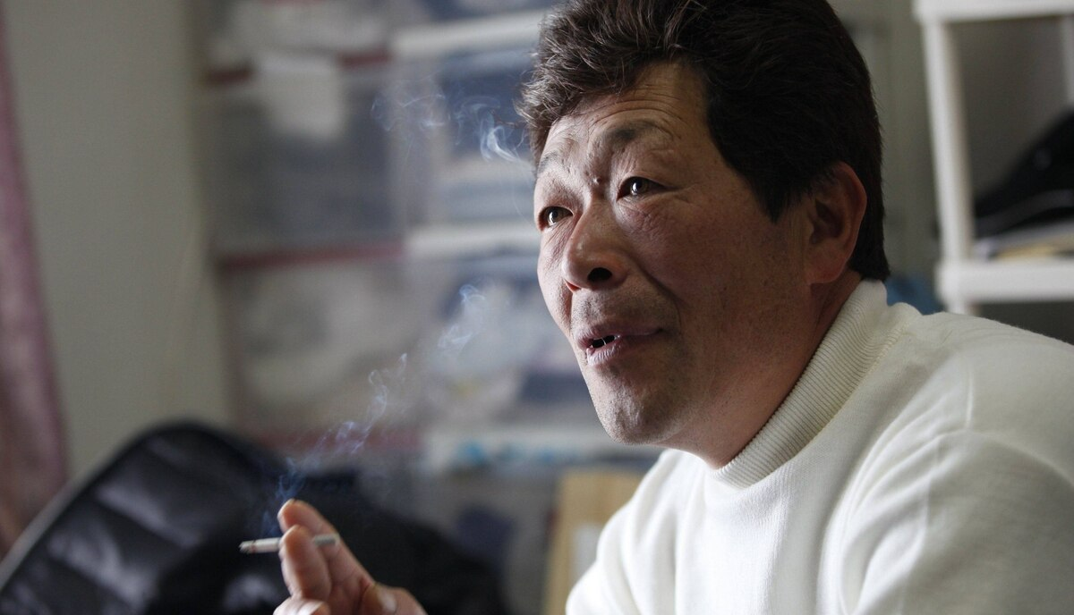 Takaaki Watanabe, 48, smokes a cigarette in his temporary home on February 24, 2012. Watanabe, a seaweed farmer, was one of the lucky 5.8 percent from his hometown whose boat survived the March 11, 2011 tsunami, however what he lost was much greater. Tsunami waves swept away his wife, mother and his house, that was built on land handed down to him through 13 generations.