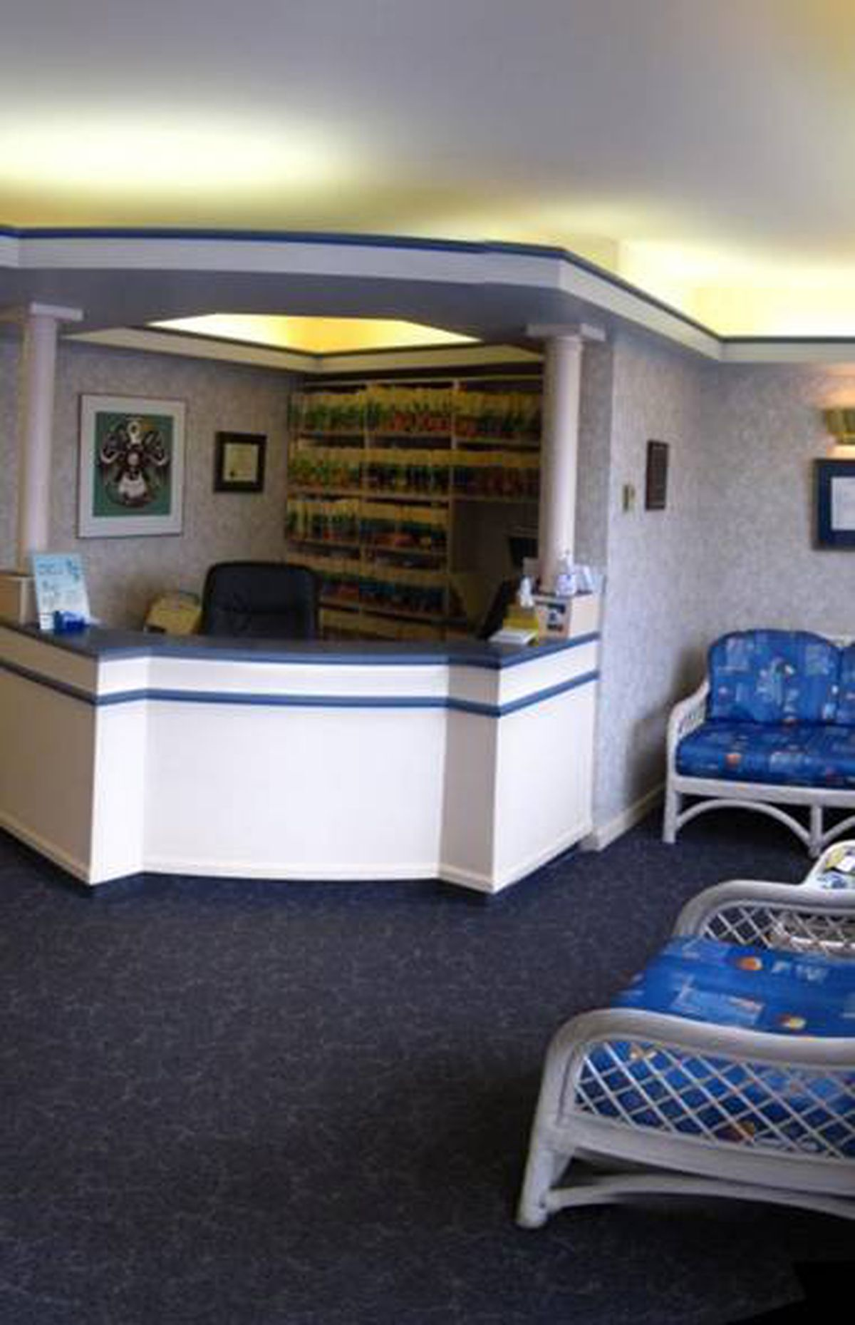 """""""I'm looking for a reception area that is more in keeping with innovative dental practices of the clinic - Dr. Adam Pite STYLE: Firstly, remove all the wallpaper and select a neutral base colour to work off of. Consider removing the carpet and replacing it with laminate floors, which is a cost effective option and reconfigure the reception desk by elimination the angles and creating a """"wrap"""" which extends to the floor. And update the artwork, hanging the new pieces lower to work better with the height of the room. STORAGE: Behind the reception desk, install a built-in storage system that would conceal the exposed filing system and create a functional featured design element. LIGHTING: Exchange the florescent lights with halogens and introduce hanging pendant lights for a warmer ambience. Also, replacing the current furniture with more modern pieces will also lighten the overall feeling of the space. - Del Terrelonge, owner and designer, Rhed Design Studio"""