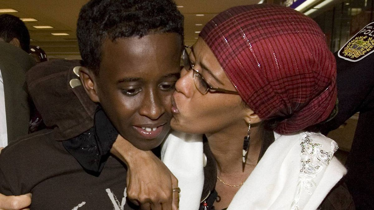 Suaad Hagi Mohamud, who was detained for three months in Kenya after authorities decided she didn't resemble her passport photo, embraces her son Mohamed Hussein upon her arrival at Pearson International Airport in Toronto on Saturday.