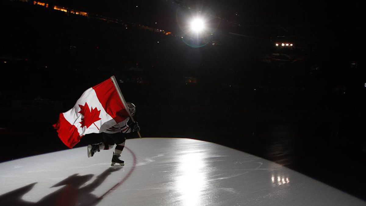 A minor hockey leaqgue player carries the Canadian flag prior to Team Canada's game against Finland.