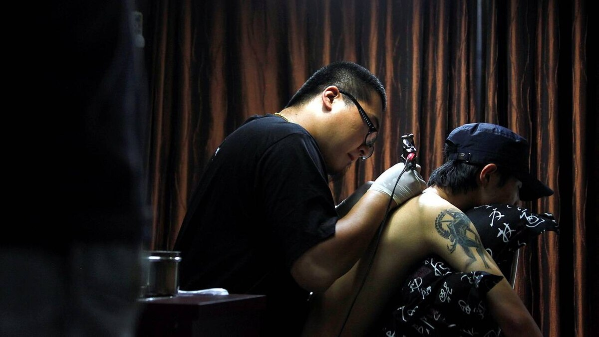 Tattoo artist Ren Liang works on a tattoo celebrating China's 60th anniversary on customer Chen Huang's back in his shop in central Beijing