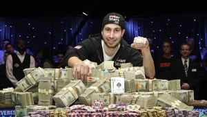 Jonathan Duhamel of Canada poses with prize money and his championship bracelet after beating John Racener of the U.S. in the finals of World Series of Poker Main Event at the Rio hotel-casino in Las Vegas, Nevada November 8, 2010.