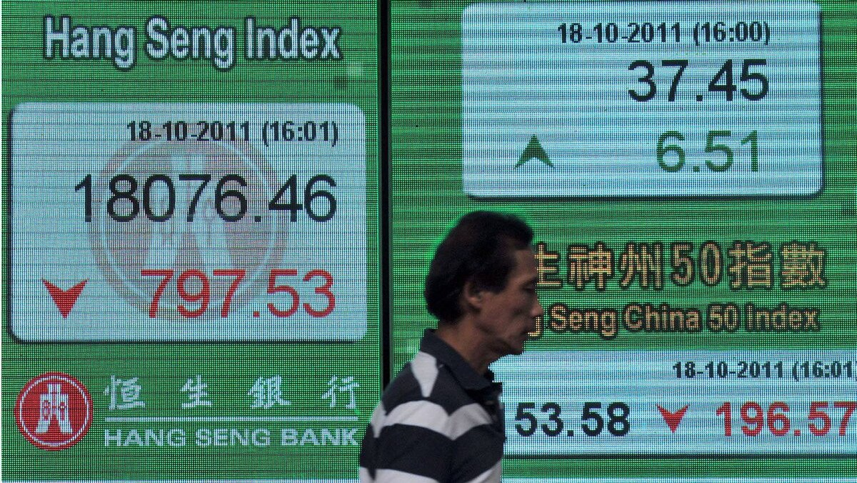 A man walks past a display board showing the Hang Seng stock market index in Hong Kong on October 18, 2011.