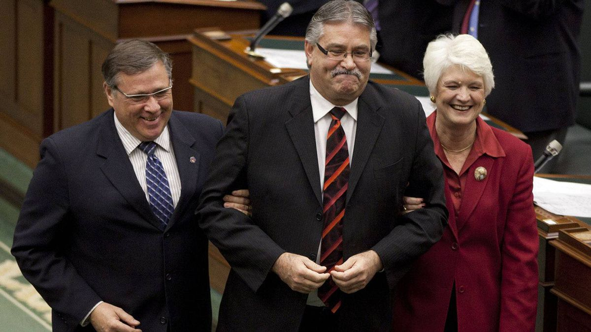 Newly elected Speaker of the Ontario Legislature, Liberal MPP Dave Levac is guided toward the Speaker's chair by fellow MPPs Jerry Ouellette and Liz Sandals at Queen's Park on Nov. 21 2011.