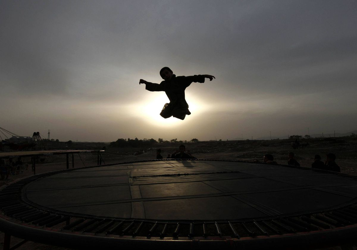 A boy is silhouetted against the sun while jumping on a trampoline on the outskirts of Islamabad, Pakistan.