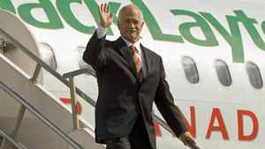 NDP Leader Jack Layton waves from his campaign plane as he arrives in Calgary on Sept. 7, 2008.
