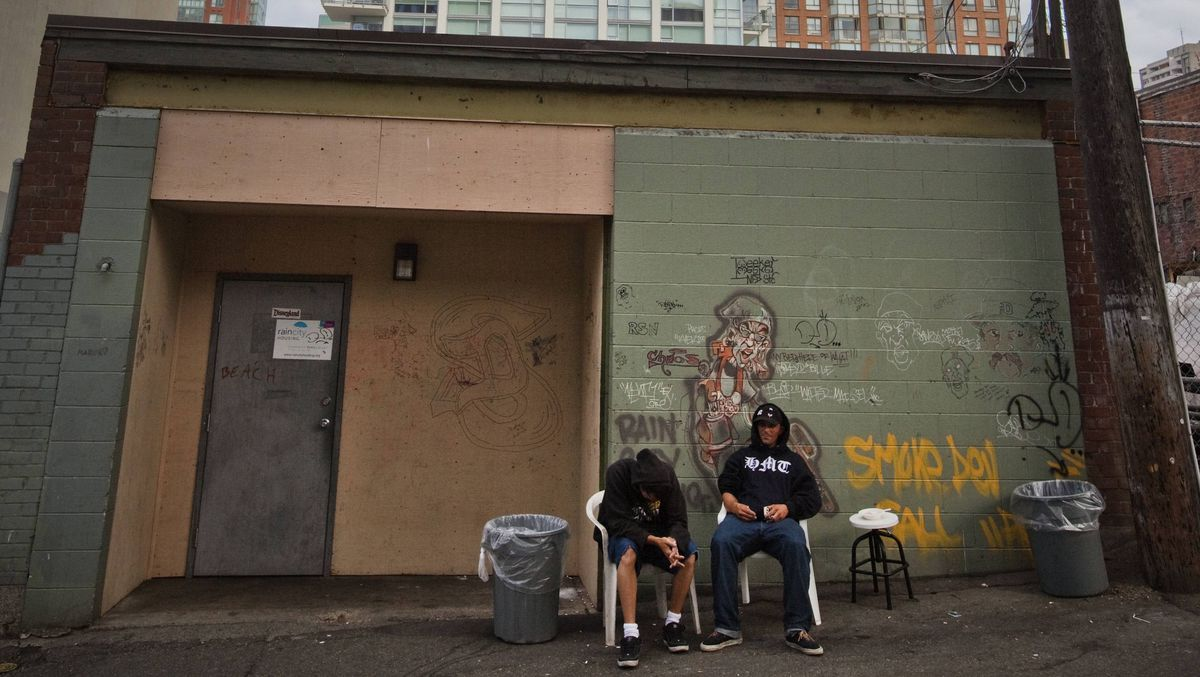 Patrons of a temporary homeless shelter run by HEAT situated in a residential neighborhood sit outside the shelter onJune 12, 2009.