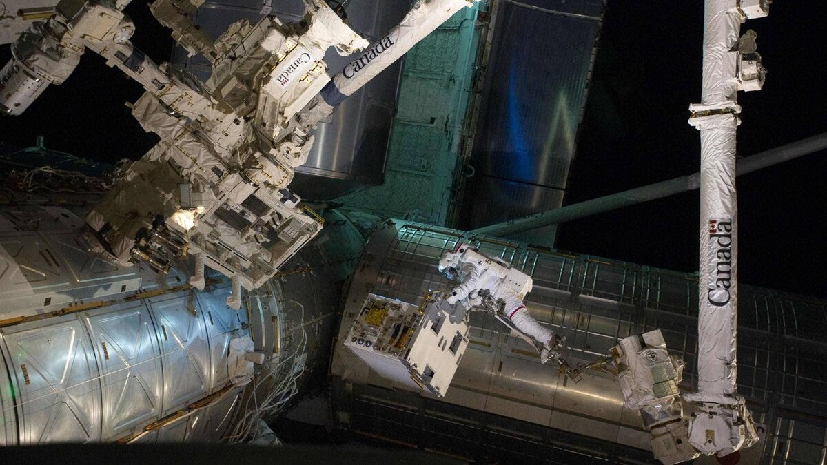 Spacewalker Ron Garan rides on the International Space Station's robotic arm as he transfers a failed pump module to the cargo bay of space shuttle Atlantis during the final spacewalk during a shuttle mission in this photo taken July 12, 2011.