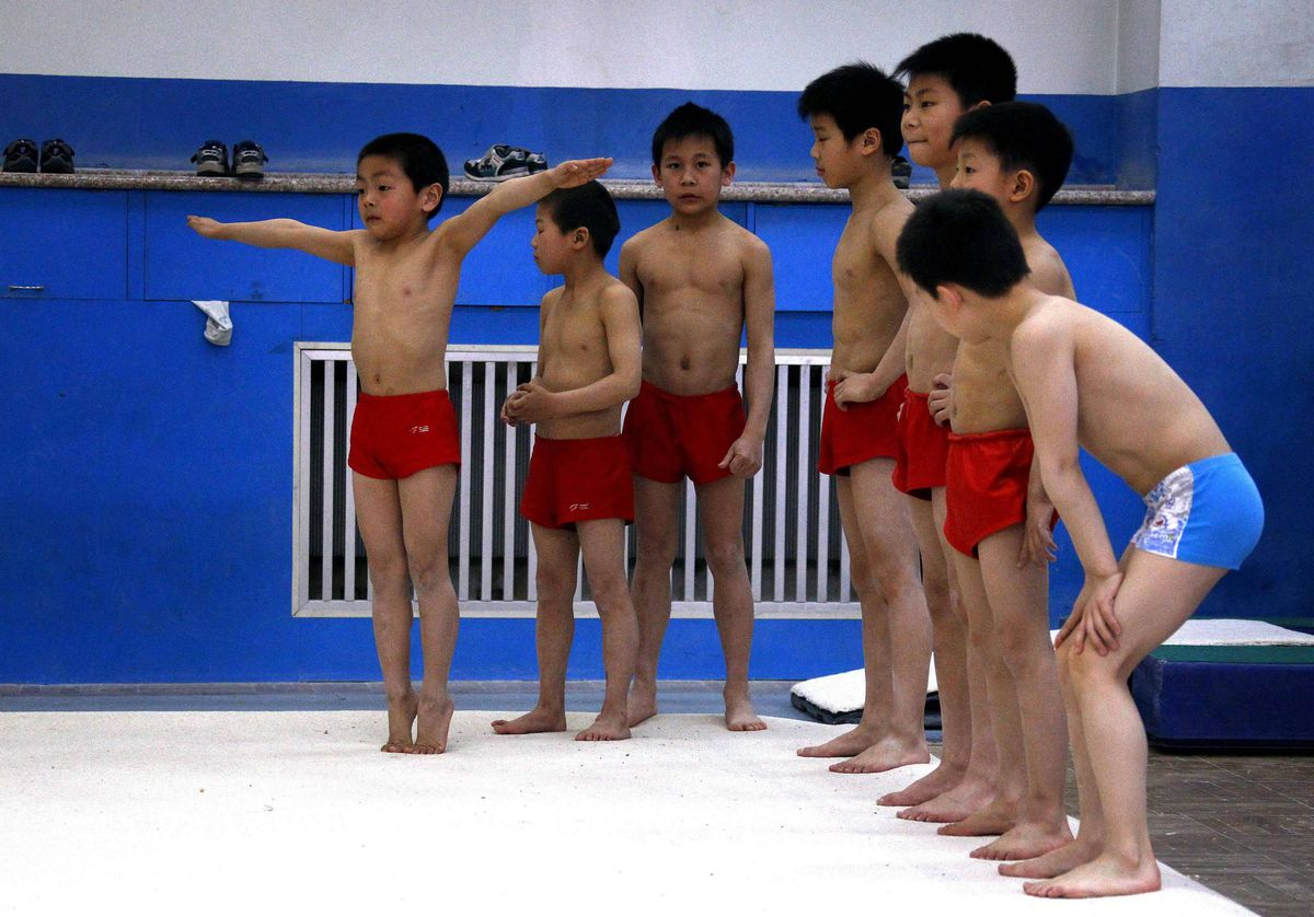 Young gymnasts prepare to practise their floor exercises during a gymnastics class.