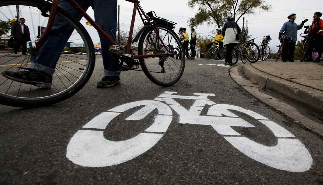 A cyclists walks by a bike lane symbol painted by activists at a memorial on Monday, November 14, for pregnant cyclist Jenna Morrison, who was recently killed after being struck by a truck at Sterling and Dundas in Toronto.