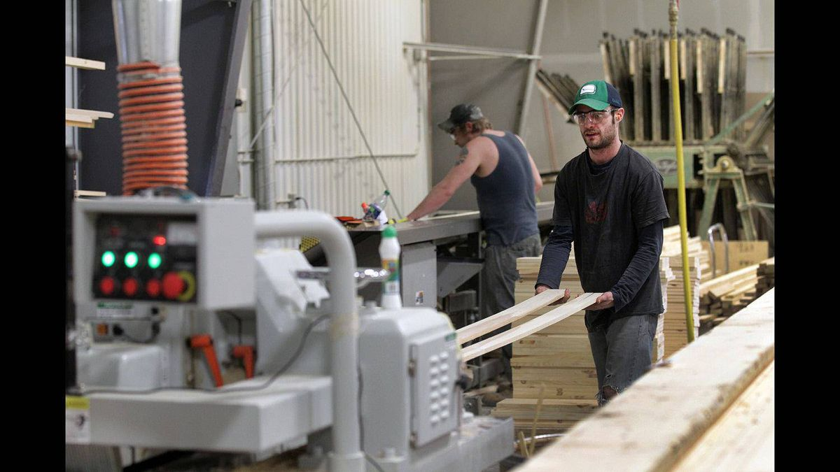 Vokes Furniture employee Matt Harwood retrieves a cut board from a machine at the company's factory.