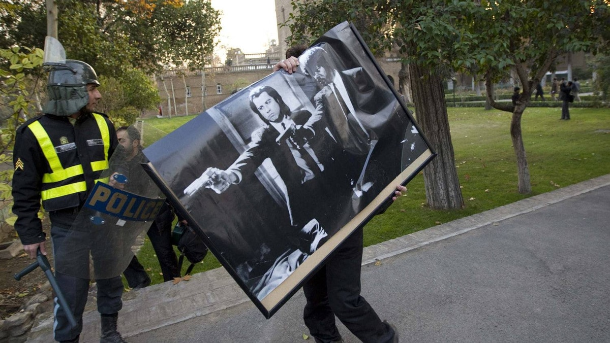 A protester walks with a poster from the British embassy in Tehran.