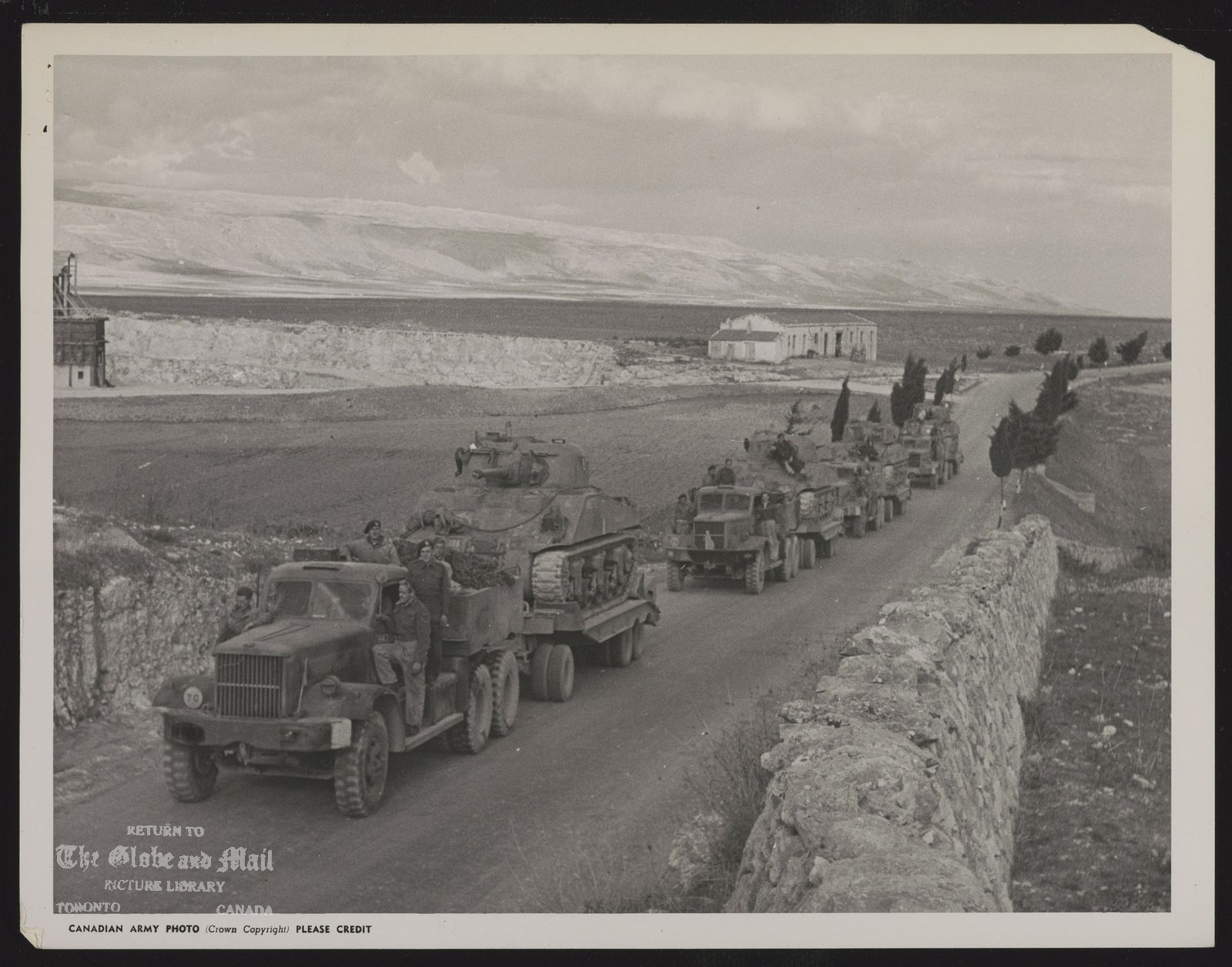 RECOVER CANADIAN TANKS FROM SEA Tanks lost in the sea by the Three Rivers Regiment in the amphibious landing which preceded the capture of Termoli, Italy, are shown here being taken away by carriers after recovery from the sea. The Three rivers Regiment destroyed 10 German tanks at Termoli in support of the Irish Brigade. (Canadian Army Overseas Photo)