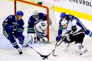 Vancouver Canucks' Michael Funk, 43, and Mario Bliznak, 62, battle with San Jose Sharks' Scott Nichol in front Canucks goalie Benn Ferriero during the first period NHL preseason action in Vancouver on Wednesday, September 23, 2009.